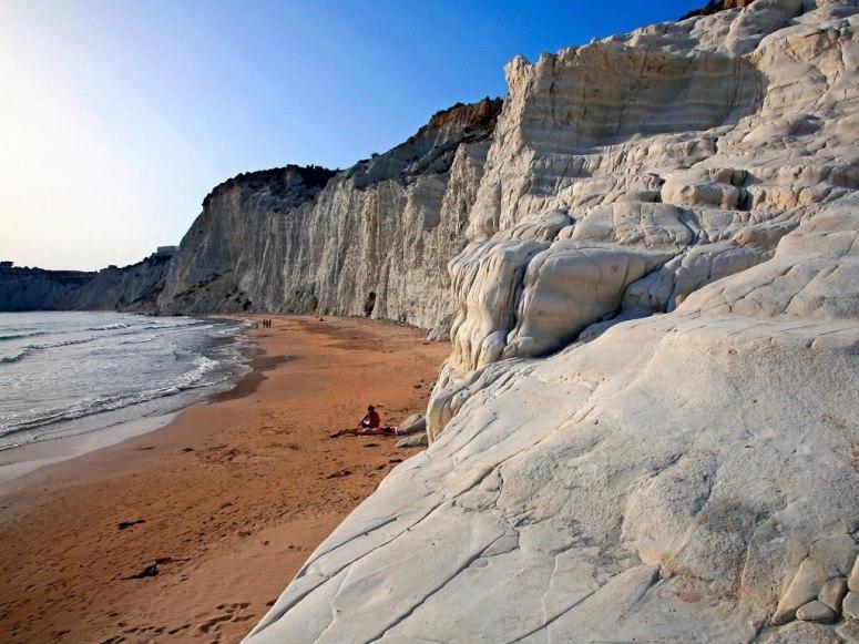 Плажът Scala Dei Turchi е поразително живописен. Неговите огнени бронзови пясъци правят зашеметяващ контраст с лазурния цвят на океана отпред, и бледите сиви скали отзад. Районът е известен като едно от най-красивите природни чудеса на Сицилия.