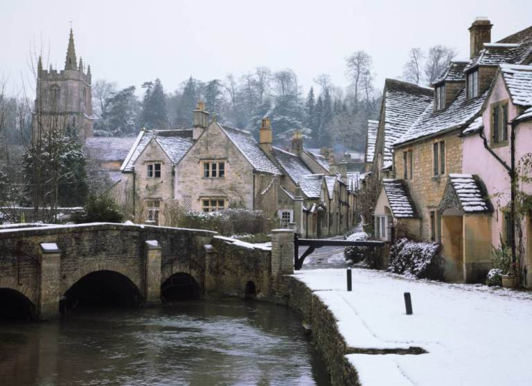 The small quintessential snow covered village of Castle Combe in Wiltshire.