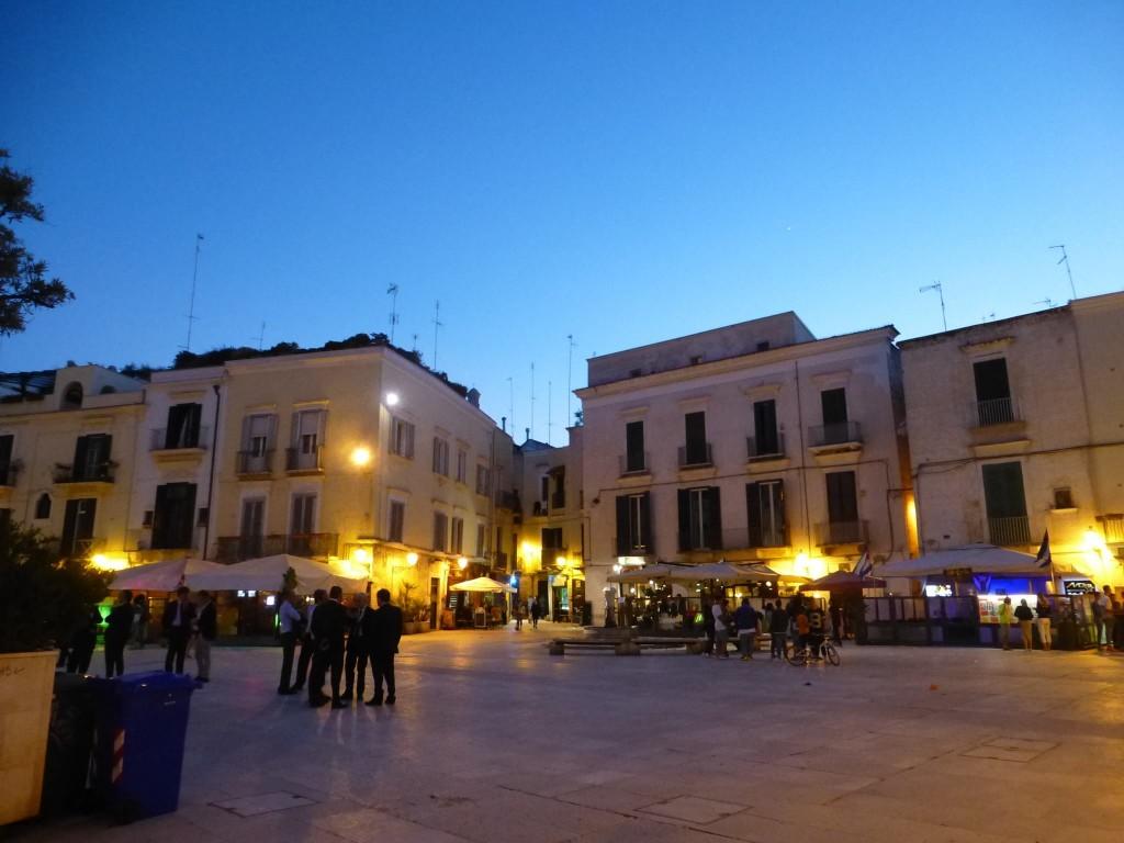 Площад в стария град, събота вечер. В средата е заведението с пандзеротитата.