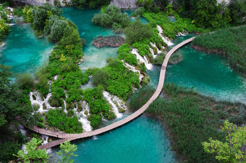 Waterfalls in Plitvice National Park. Aerial view. One lake flows into another surrounded by lush vegetation. Water has natural vivid turquoise color. Popular touristic attraction.